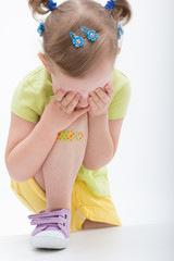 Crying little girl with plaster on knee