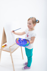 Little girl painting on easel
