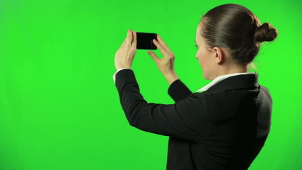 Businesswoman against a green screen uses mobile phone camera