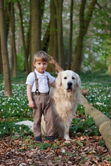 Two years old boy with his dog outdoor portrait