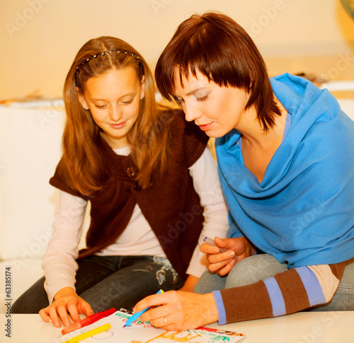 Mother and her daughter drawing.