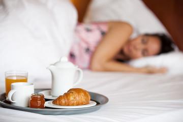 Schlafende Frau mit Frühstück im Hotelbett