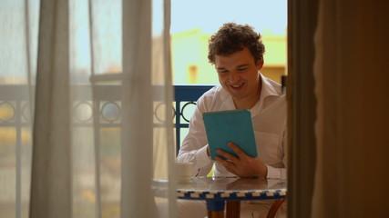 Man with laptop having tea on the balcony