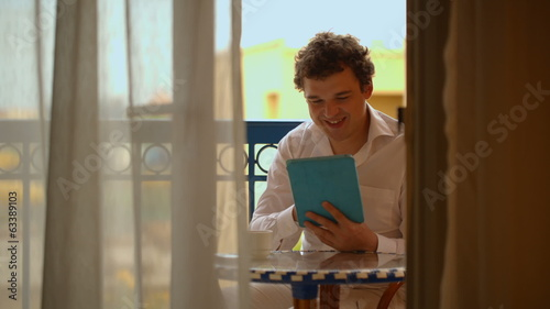 Man with laptop having tea on the balcony
