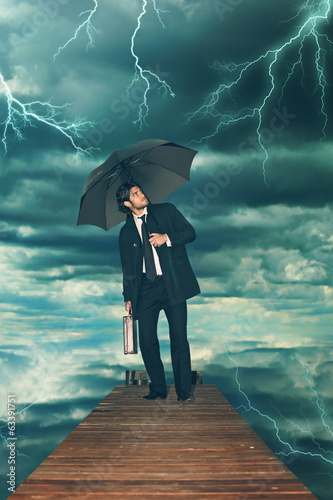 Businessman with umbrella facing storm