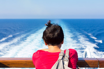 girl looks at a ship on the horizon