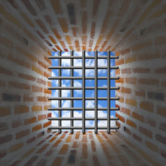 Prison's window and bars in wall from brick