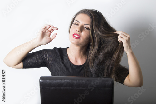 Gorgeous woman playing with her hair in the studio