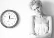 Conceptual portrait of woman with big clock.