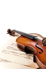 Old scratched violin on music sheet. White background.