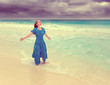 woman in long blue dress in surf of stormy sea,retro effect