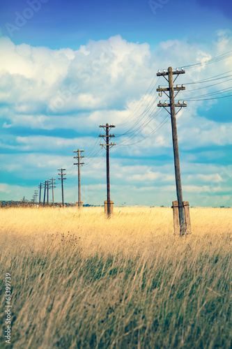 Old wooden electric pillar in the field,with a retro effect