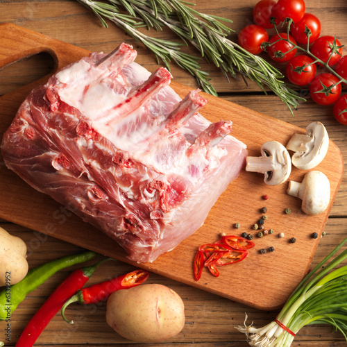 canvas print picture Slice of raw beef with fresh rosemary