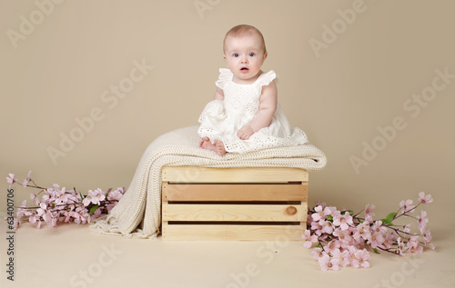 Baby Girl with Cherry Blossom Flowers in Spring Dress on Blanke