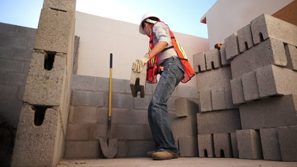 Woman Lifts Brick on Construction Site