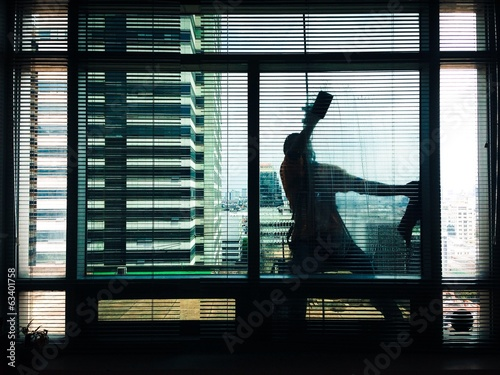 silhouette of a man cleaning building glass