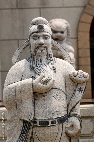 Statues of Chinese deity and lion sculpture.
