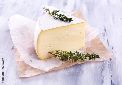 Tasty Camembert cheese with thyme, on wooden table