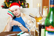 Young man with hangover in Santa hat
