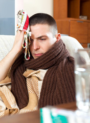 Sad  man having headache holding towel on head