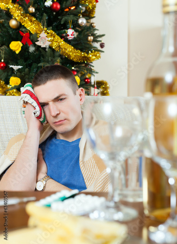 Man having hangover during  holidays at home