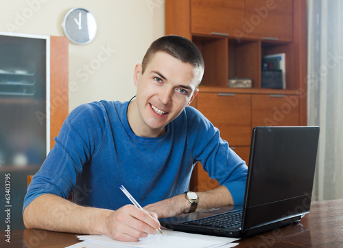guy staring financial documents at table