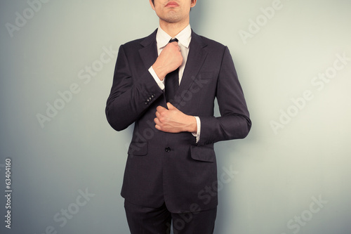 Young businessman adjusting his tie