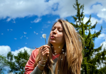 Beautiful woman blowing on dandelions