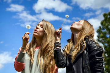 Two young woman are blowing on dandelions