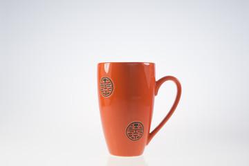 tazza arancio/rosso su sfondo bianco
