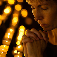 Prayer praying in Catholic church near candles. Religion concept