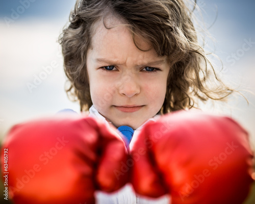 Kid wearing red boxing gloves