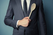 Businessman holding a wooden spoon