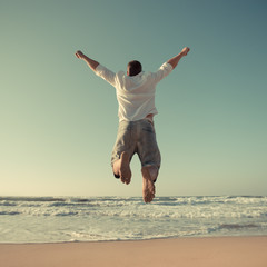 Funny man jumping at the beach