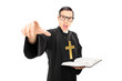 Angry priest pointing towards the camera