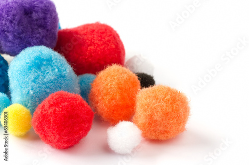 Colorful fluffy pom poms on a white background