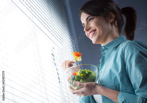 Young woman eating salad