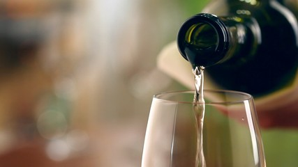 Pouring white wine into glass