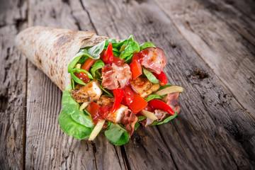 Chicken strips in a Tortilla Wrap on wood.