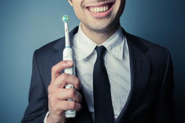 Businessman brushing his teeth