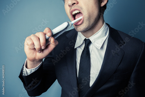 Businessman brushing his teeth