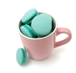 mint macarons in pink cup over white
