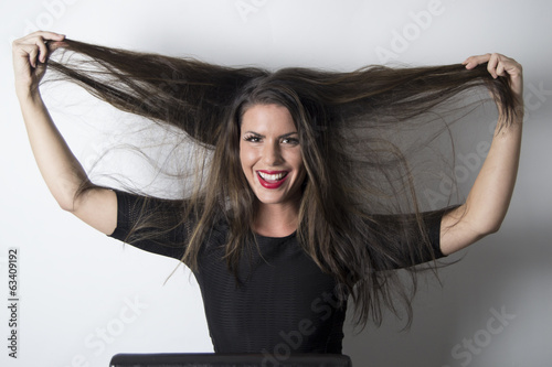 Happy gorgeous woman with long brown hair (studio, portrait)
