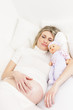 pregnant woman sleeping in bed with a doll