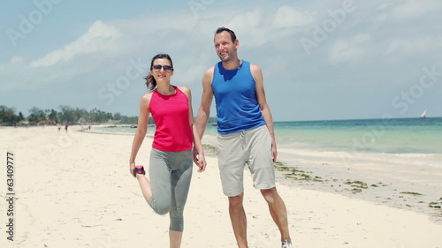 Young couple stretching before jogging on beautiful beach