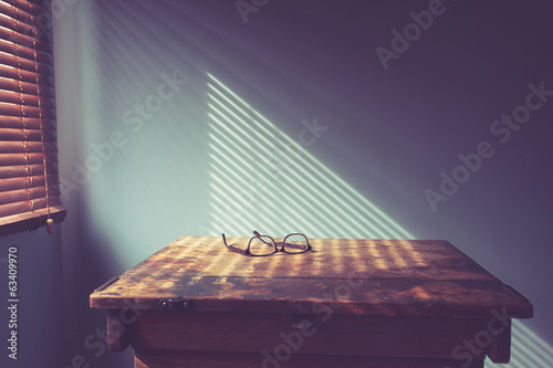 Glasses on desk by window