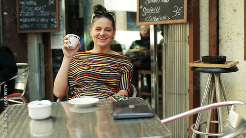 happy woman drinking coffee by the table and smiling to the came