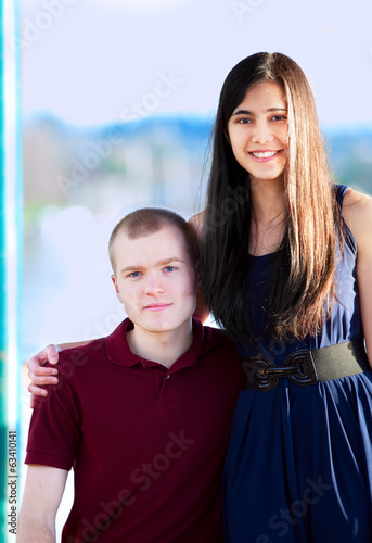 Young woman standing next to seated young man by a lake