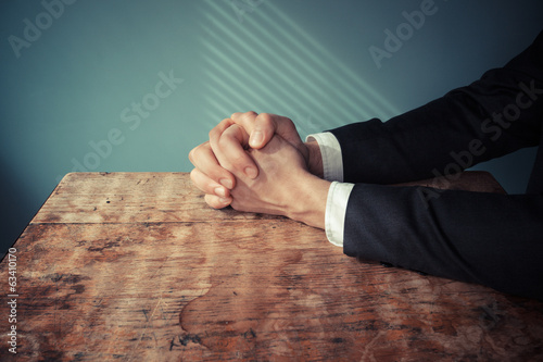 Man in suit praying at desk