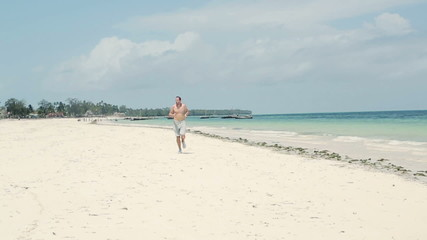 Young man jogging on beautiful beach, slow motion